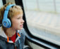 Boy with autism wearing headphones and looking out of train window
